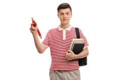 Tonårs- student som rymmer en blyertspenna och böcker royaltyfria bilder