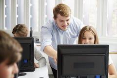 Tonårs- studenter som studerar i IT-grupp med läraren royaltyfri fotografi