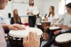 Tonårs- studenter som studerar slagverk i musikgrupp arkivbilder