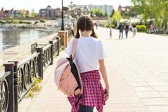 Tonårs- studentflicka som går ner gatan med ryggsäcken Dra tillbaka till skolan, baksidasikt arkivfoton