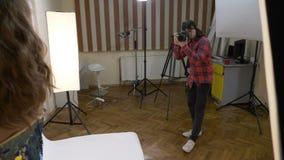 Tonårs- studentfoto som hemma skjuter hans flickvän med en yrkesmässig kamera i en improviserad studio i vardagsrummet - arkivfilmer