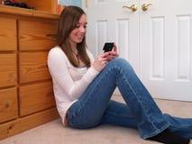 tonårs- texting för flickatelefon Royaltyfria Foton
