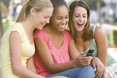 tonårs- utvändig sitting för flickor royaltyfri bild