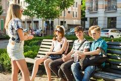 Tonårs- vänner flicka och pojkesammanträde på bänken i staden som talar Kamratskap och folkbegrepp arkivbild