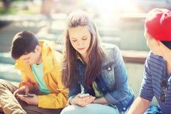 Tonårs- vänner med smartphones utomhus arkivbilder
