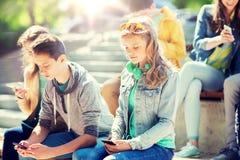Tonårs- vänner med smartphones utomhus arkivfoto