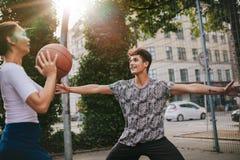 Tonårs- vänner som mot varandra spelar streetball Royaltyfria Foton