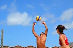 Tonårs- vänner som spelar volleyboll Arkivbild