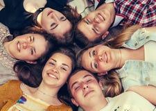 Tonårs- vänner som tillsammans ligger i cirkel Arkivbilder