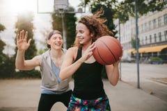 Tonårs- vänner som tycker om en lek av streetball Royaltyfri Fotografi