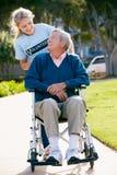 Tonårs- volontär som skjuter den höga mannen i rullstol Fotografering för Bildbyråer