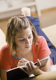 tonårs- writing för bokflicka Royaltyfri Foto