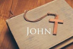 Ton de vintage de collier croisé chrétien en bois sur des WI de Sainte Bible Photographie stock libre de droits