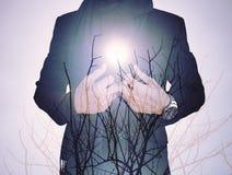 Ton de vintage, double exposition, homme d'affaires avec les branches sèches contre le soleil Photo stock