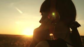 ton?rig flicka som lyssnar till musik och h?ller ?gonen p? solnedg?ngen Lycklig flickadans i hörlurar i strålarna av ett härligt stock video