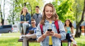 Ton?rig studentflicka med skolap?sen och smartphonen royaltyfria foton