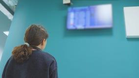 Ton?rig turist- ung flicka h?lla ?gonen p? flygschemat av hennes avvikelse flygplatsen se informationsbrädet lager videofilmer