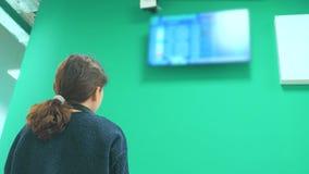 Ton?rig turist- ung flicka h?lla ?gonen p? flygschemat av hennes avvikelse flygplatsen se informationslivsstilbrädet stock video
