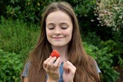 Ton?rs- flicka som ?ter en jordgubbe arkivbild