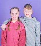 Ton?rv?nner Riktigt kamratskap f?r flicka och f?r pojke Barn som ler framsidor p? violett bakgrund V?nkram Barns dag arkivfoto