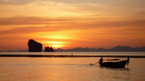 Ton Sai Sunset. Sun sets behind limestone karsts, a figure walks across the shot, a long-tail boat moves in the foreground.  Taken near Ton Sai, Krabi, Thailand Royalty Free Stock Photos