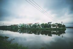 Ton Vietnam Damm i centrumstad på bakgrund Tv?-v?ning herrg?rdar p? sj?n oklarheter reflekterat vatten royaltyfri foto