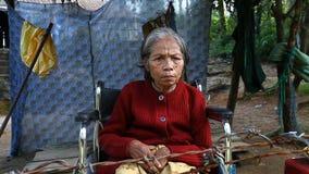 Ton Vietnam-December 25,2016: ett vuxet vietnamesiskt kvinnasammanträde i en rullstol frågar för allmosa från turister som passer arkivfilmer