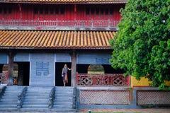 Ton/Vietnam, 17/11/2017: Kvinnaanseende inom ett traditionellt hus med det dekorativa belade med tegel taket i citadellen av tone royaltyfri bild