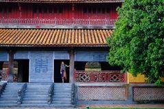 Ton/Vietnam, 17/11/2017: Kvinnaanseende inom ett traditionellt hus med det dekorativa belade med tegel taket i citadellen av tone arkivfoto