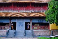 Ton/Vietnam, 17/11/2017: Par som står inom ett traditionellt hus med det dekorativa belade med tegel taket i citadellen av tonen, arkivbild