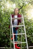 Tonad bild av den lyckliga tonårs- flickan som poserar på trappstegen på äpplet Arkivfoton