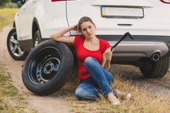 Tonad bild av för bilhjul för ung kvinna som den hållande skiftnyckeln kämpar för att ändra det plana gummihjulet i fält Arkivbild