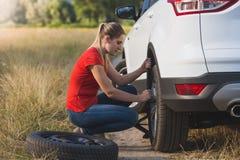 Tonad bild av gummihjulet för bil för ung kvinna det ändrande plana med det extra- fältet i fält Arkivfoton