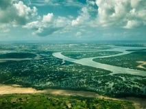 Tonad bild från fönstret av ett flygplan av flod- och våtmarkskogen med staden av Mombasa i bakgrunden med himlen Arkivbilder