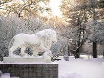 Tonad bildskulptur av ett lejonanseende på en sockel i vintern i St Petersburg mot bakgrunden av dettäckte trädet royaltyfri foto