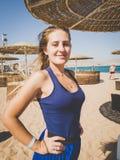 Tonad closeupstående av den härliga le unga kvinnan med långt hår på stranden på den blåsiga dagen royaltyfri foto