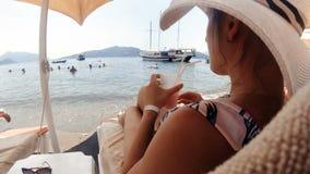 Tonad closeupvideo av den härliga unga kvinnan i hatt som kopplar av på stranden och dricker coctailen arkivfilmer