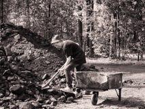 Tonad smutsig pys för bild med en skyffel i hans händer som ställningar bredvid järnspårvagnen och grävakol mot bakgrunden av Arkivfoton