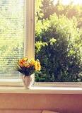 Tonad sommarguling blommar på widnow - fönsterbräda Royaltyfri Fotografi