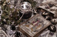 Tonad stilleben med den svarta stearinljuset, runor och tarokkorten Fotografering för Bildbyråer