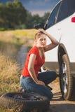 Tonat foto av den ledsna unga kvinnan som försöker att ändra det plana gummihjulet för bil på den öde vägen på fältet Royaltyfri Bild