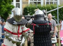 Two full contact warriors wearing armour from west and east stock photos