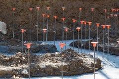 Tondo per cemento armato con i cappucci di sicurezza arancio che sporgono dai basamenti concreti versati immagine stock