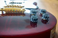 Tone And Volume Knobs On a Shiny Wine Red Guitar With Golden Hardware Placed On A Wooden Table royalty free stock photo