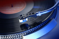 Tonearm from classic turntable. Tonearm from a 70ies era turntable with needle on vinyl record and lit with a blue light stock photos