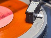 Tonearm of record-player on orange vinyl disc. Close up Stock Photo