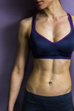 Athletic female abs. The toned abs of an athletic young woman wearing a sports bra Stock Photos