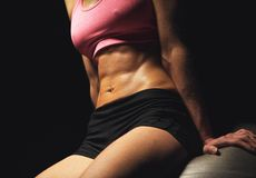 Toned Abs of a Fitness Woman. Closeup of a fitness woman's toned abs Stock Image