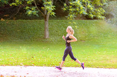 Toned athletic woman enjoying a morning jog. Toned athletic young blond woman enjoying a morning jog through a lush green park in a health and fitness concept Royalty Free Stock Images