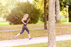 Toned athletic woman enjoying a morning jog. Toned athletic young blond woman enjoying a morning jog through a lush green park in a health and fitness concept Stock Photo
